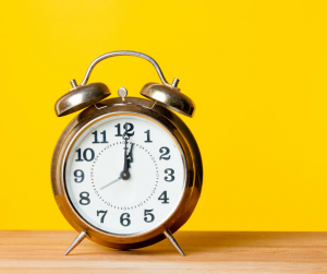 Golden alarm clock on yellow background